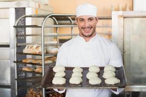lächelnder Bäcker, der Tablett des rohen Teigs hält foto