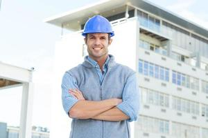 Stehende Arme des männlichen Architekten verschränkten außerhalb des Gebäudes foto