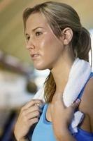 Frau mit Handtuch um den Hals schaut weg im Fitnessstudio foto