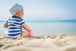 kleiner Junge sitzt auf dem Sand foto