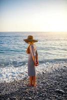 Frau im entkleideten Kleid mit Hut am Strand foto