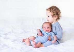 entzückendes Kleinkindmädchen, das ihren neugeborenen kleinen Bruder hält foto