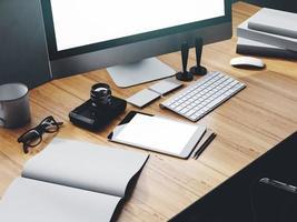 Foto des modernen Arbeitsbereichs mit Desktop-Bildschirm, Tablet, Kamera, Tastatur