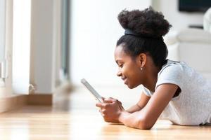 Afroamerikanerfrau, die eine taktile Tablette verwendet foto