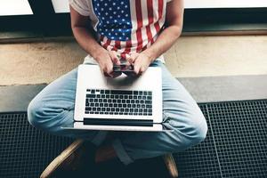 junger Student, der auf dem Boden sitzt, soll Nachrichten am Telefon foto