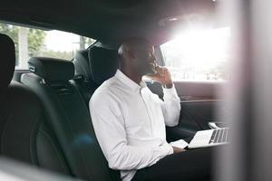 junger Unternehmer, der während der Reise ins Büro arbeitet foto