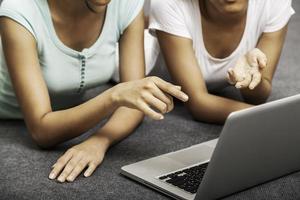 junge Frauen, die beim Verwenden des Laptops liegen foto
