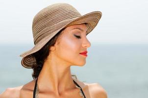 Frau mit einem Sonnenhut an einem tropischen Strand