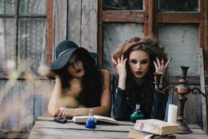 Zwei Vintage-Hexen führen ein magisches Ritual durch foto