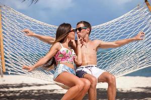 romantisches Paar, das sich in der Strandhängematte entspannt