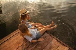 zwei Mädchen, die nahe Fluss entspannen foto