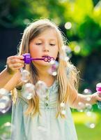 kleines Mädchen mit Seifenblasen foto