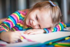 kleines süßes Mädchen, das mit Stiften malt foto