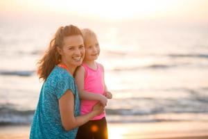 Porträt der glücklichen Mutter und Tochter am Strand bei Sonnenuntergang