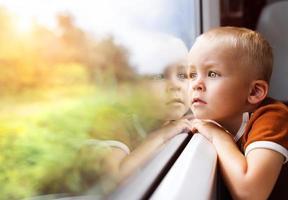 kleiner Junge, der im Zug reist foto