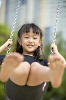 junges asiatisches Mädchen, das glücklich im Park spielt foto