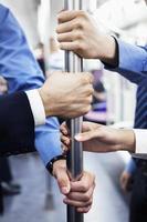 Nahaufnahme von vier Geschäftsleutenhänden, die Stange auf U-Bahn halten