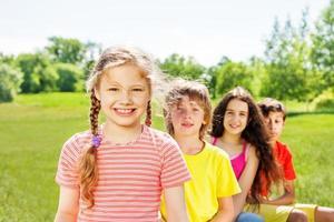 glückliches Mädchen mit Zöpfen und ihren drei Freunden foto