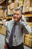 lächelnder Manager, der in einem Headset spricht foto