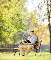 älterer Mann mit dem Sitzen auf der Bank und dem Lesen eines Romans foto