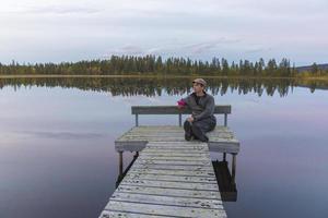 Mann sitzt auf Landungssteg am See foto