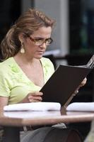 Frau liest Menü außerhalb des Restaurants foto