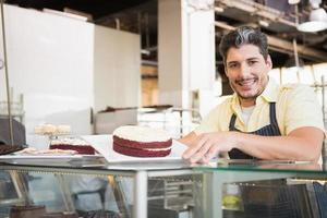 lächelnder Arbeiter, der roten Samt zeigt foto