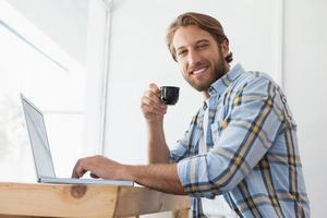 Gelegenheitsmann mit Laptop, der Espresso trinkt