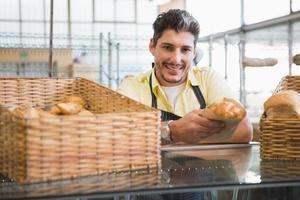 lächelnder Kellner in der Schürze, die Brot hält foto
