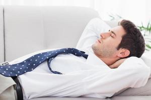 Geschäftsmann, der auf dem schlafenden Sofa liegt foto