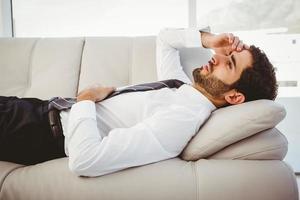 kranker Geschäftsmann, der auf der Couch liegt foto