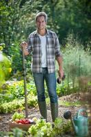 Gärtner mit einer Gemüsekiste zu seinen Füßen foto