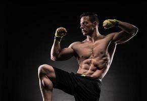 muskulöser Mann im Studio auf dunklem Hintergrund foto