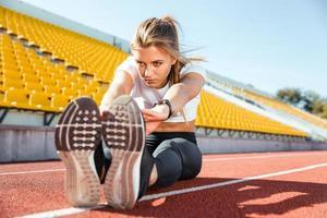 Frau streckt sich auf dem Boden im Stadion foto