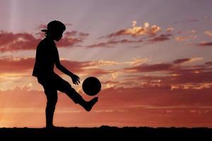 Silhouette eines Jungen, der Fußball oder Fußball an der spielt foto