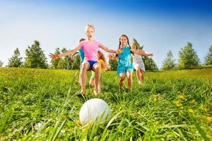 Gruppe von Kindern, die zum Ball in der Wiese laufen foto