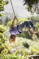 Junge, der an einem Seil schwingt, das von einem Baum gebunden wird foto