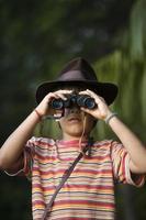 Junge mit Abenteurerhut beobachtet mit Fernglas.