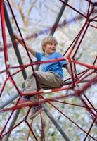 Junge klettert am Spielplatz