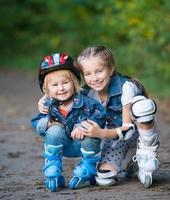 zwei kleine Mädchen auf Rollen