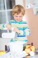 lustiger blonder Junge, der Apfelkuchen drinnen backt foto