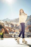hübsches Mädchen Eislaufen im Freien an der Eisbahn