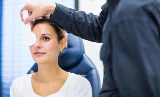 hübsche junge Frau, deren Augen durch Optometrie untersucht werden