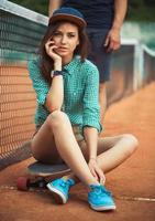 Mädchen sitzt auf einem Skateboard auf dem Tennisplatz