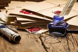 blaues Tintenfass und Gläser auf dem Tisch mit alten Nachrichten gefüllt.