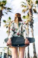 stilvolle Frau mit Penny Board, das gegen tropischen Himmel steht foto