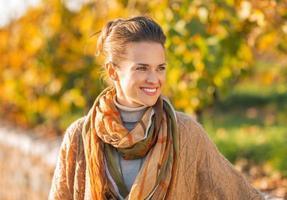 glückliche junge Frau im Herbst im Freien, die auf Kopienraum schaut