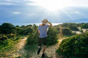 glückliche Frau, die im Feld bei Sonnenuntergang springt. Frühlingsfreiheit foto