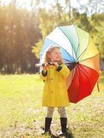positives Kind mit buntem Regenschirm am Herbsttag foto