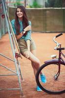schönes junges Mädchen mit Longboard und Fahrrad